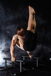 Muscular build man doing calisthenics on parallels bar indoor on black, smoked background. concept of healthy lifestyle and power