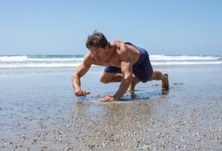 Muscular Caucasian man doing bear crawl workout on sandy beach on sunny day at lowtide