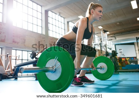 Muscular caucasian woman in a gym doing heavy weight exercises. Young woman doing weight lifting at health club.