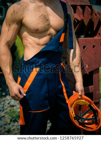 Muscular concept. Muscular body in working uniform. Muscular activity. Muscular strength and power. #1258765927