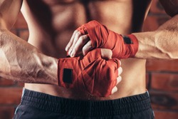 Muscular Fighter kickbox  With Red Bandages against the background of a brick wall