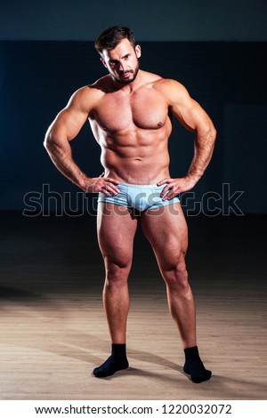 Muscular fitness man antique statue perfect muscles six pack abs and sexy bare nude chest bodybuilder  model posing black background in the studio. competition functional training workout gym