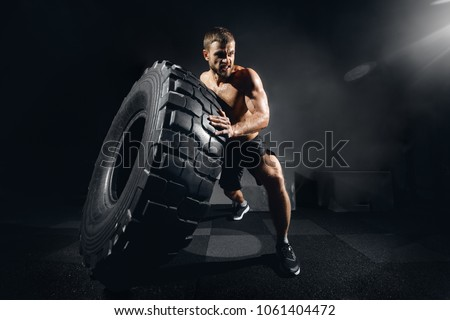 Muscular fitness shirtless man moving large tire in gym center, concept lifting, workout cross fit training #1061404472