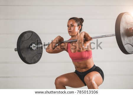 Muscular fitness woman deadlift a barbell over his head in the gym. Sports, cross fit and fitness - concept of healthy lifestyle. Woman in the fitness club.