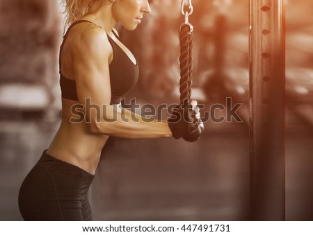 Stock Photo Muscular fitness woman doing exercises.Concept of healthy lifestyle. Cross fit bodybuilder  in the gym.