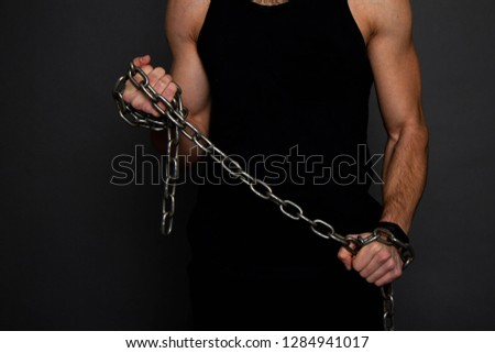 Muscular guy holding a chain. Photo exercise in the gym. go in for sports.