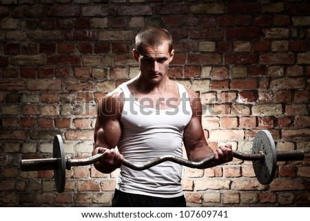 Muscular guy is training  biceps with barbell against a brick wall