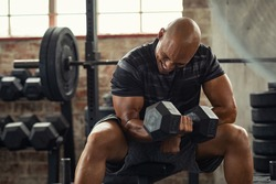 Muscular guy lifting dumbbell while sitting on bench at gym. Mature african athlete using dumbbell during workout. Strong man under physical exertion pumping up bicep muscle with heavy weight.