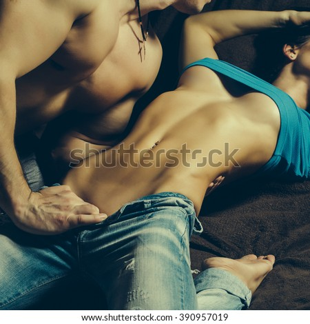Muscular handsome man undressing young sensual woman with bare belly and beautiful chest in torn sexy jeans lying indoor on wooden background closeup, square picture