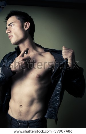 muscular handsome Man with perfume bottle wearing jacket
