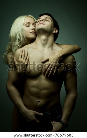 muscular handsome sexy guy with pretty woman, on dark background, glamour green light