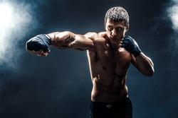 Muscular kick-box or muay thai fighter punching in smoke.