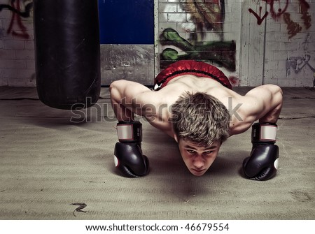 Muscular looking boxer doing press-ups in a graffiti clad suburban basement Focus on the dorsal muscles and biceps