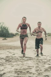 Muscular male and female athlete covered in mud running down a rough terrain with a desert background in an extreme sport race with grungy textured finish