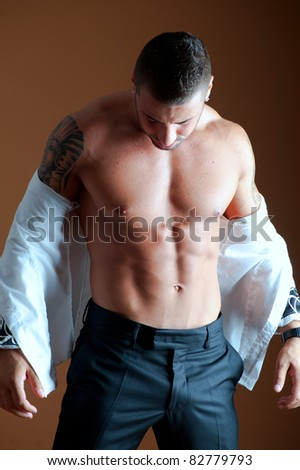Muscular male body on brown background