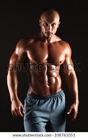 Muscular male bodybuilder on black background