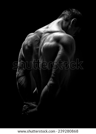 Muscular male model bodybuilder preparing for fitness training, turned back. Studio shot on black background. Black and white photo.