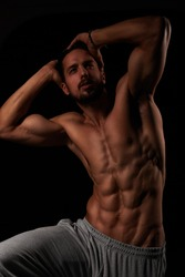 Muscular male model showing his muscular torso with his hands behind his head