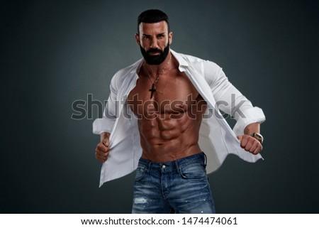 Muscular Male Model Wearing Unbuttoned White Shirt Exposing His Muscular Torso