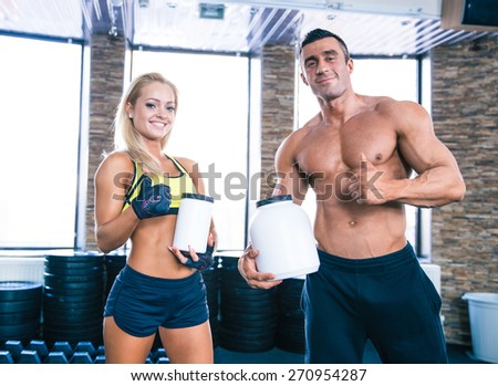 Muscular man and sporty woman holding container with sports nutrition and showing thumb up
