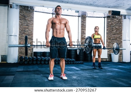 Muscular man and woman workout with barbell at gym