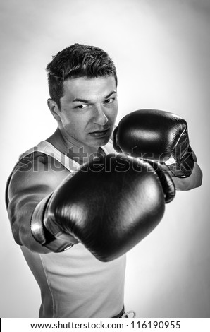 Muscular man boxing black and white