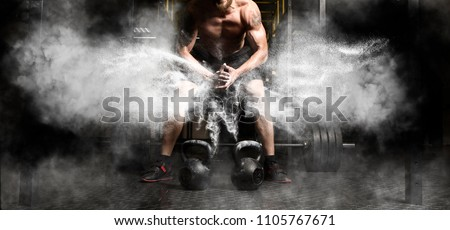 Muscular man clapping hands and preparing for workout at a gym