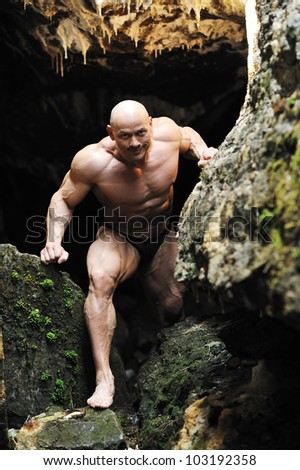 Muscular man climbs out of the cave