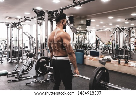 Muscular Man Doing Heavy Deadlift Exercise. Young athlete getting ready for weight lifting training