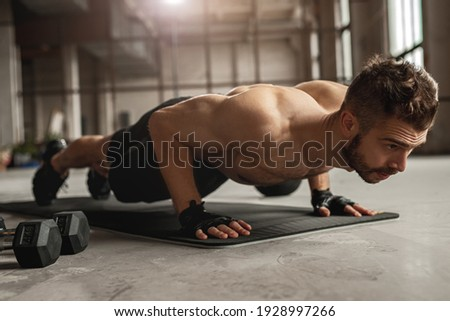 Muscular man doing push up exercise on mat near dumbbells during intense fitness workout in grungy gym Foto stock ©