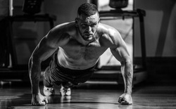 Muscular man doing push-ups on one hand against gym background. Man doing push-ups. Muscular and strong guy exercising. Slim man doing some push ups a the gym. Black and white.