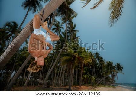 Muscular man doing upside down yoga on palm tree