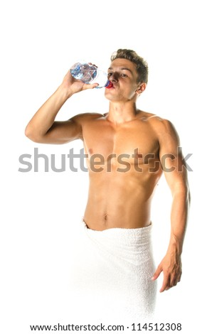 Muscular man drinking water against white background
