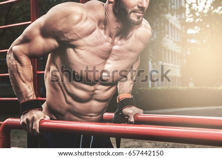 Muscular man during his workout on the street #657442150