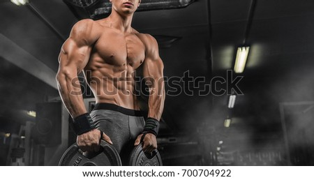 Muscular man during workout in the gym #700704922