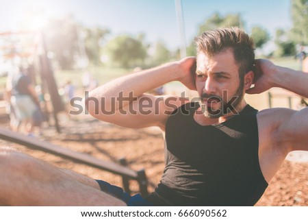 Muscular man exercising doing sit up exercise. Athlete with six pack, white male, Outdoor training. Sports and healthy lifestyle. Bearded black-haired guy doing crunches Outdoors