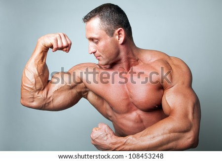 Muscular man flexing his biceps - studio shot