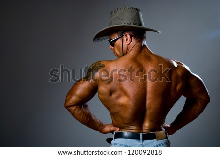 Muscular man in a cowboy hat and sunglasses on a gray background