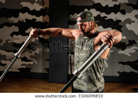 Muscular man in a sports uniform does an exercise on triceps holding barbells from a barbell