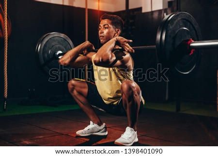 Muscular man in gym doing heavy weight exercises. Young man doing weight lifting at health club