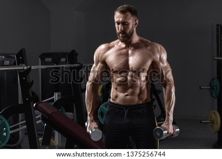 Muscular man in gym with dumbbells. Strong male naked torso abs, workout