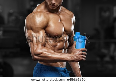 Muscular man in gym with shaker, shaped abdominal. Strong male naked torso abs, working out