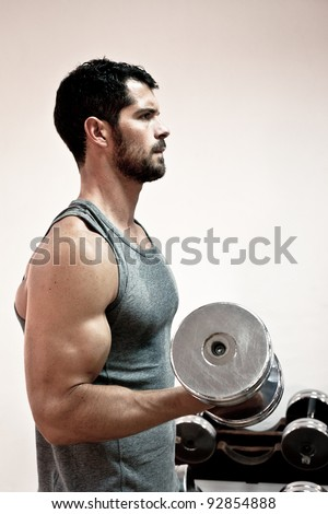 Muscular man lifting weights. Side view.