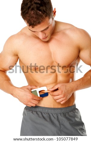 Muscular man measures level of fat on his body on white background