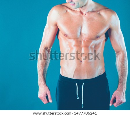 muscular man. Muscular man on a grey background showing muscles. Fitness instructor. Fitness professional. Workout. Men's fitness.