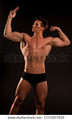 muscular man. muscular man with abs. muscular man bodybuilder point on his muscle. biceps and triceps of muscular man athlet. keeping his body in good shape #1151007020