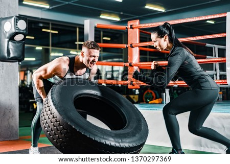 muscular man pushing a cargo bus in the gym. female coach encourages sports guy. concept motivation to overcome efforts
