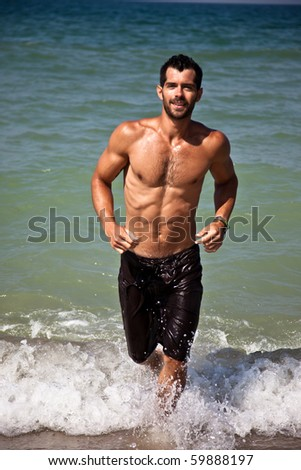 Muscular man running towards the camera from the seashore smiling.