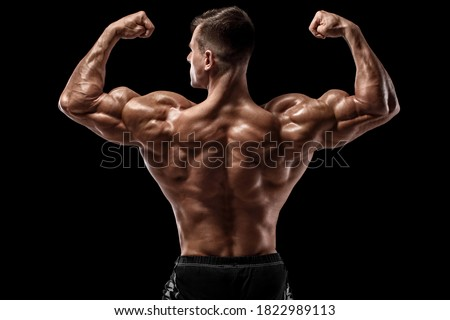 Muscular man showing back muscles, isolated on black background. Strong male rear view Photo stock ©