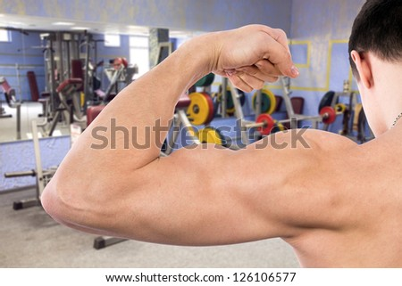 muscular man showing biceps in fitness room